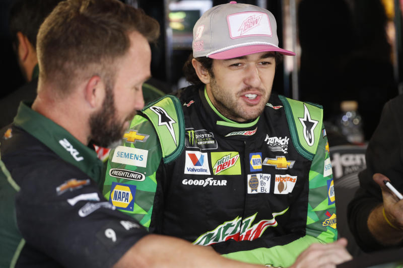 Chase Elliott talks with a crew member in the garage at Martinsville Speedway In Martinsville, Va., Saturday, Oct. 26, 2019. Elliott had an engine failure less than five minutes into the opening practice for the third round of NASCAR's playoffs. (AP Photo/Steve Helber)