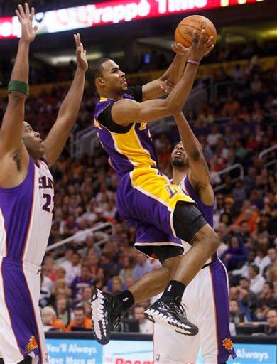 Los Angeles Lakers' Ramon Sessions drives past Phoneix Suns' Michael Redd, left, and Markieff Morris, right, during the first half of an NBA basketball game, Saturday, April 7, 2012, in Phoenix. (AP Photo/Matt York)