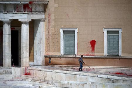 A worker cleans paint thrown by unknown attackers at the facade of the Parliament building in Athens, Greece, May 21, 2019. REUTERS/Costas Baltas