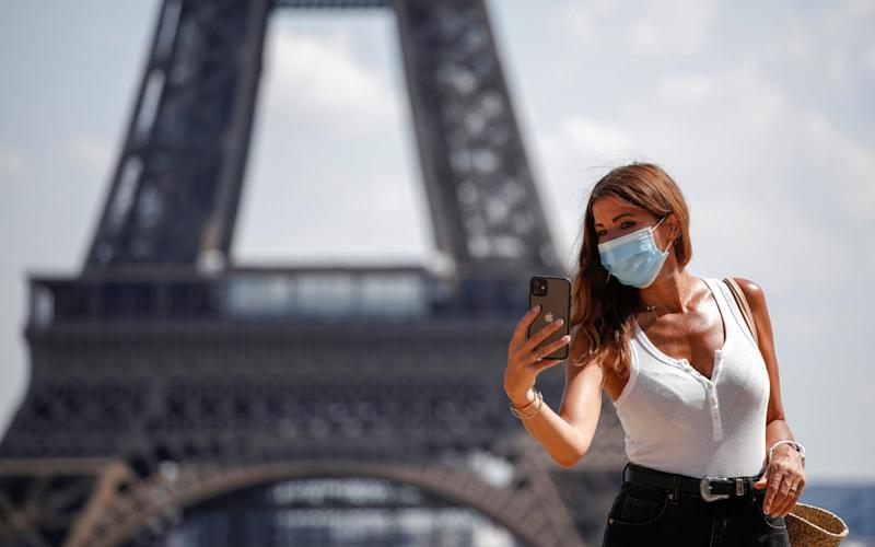 A woman wears a protective face mask - BENOIT TESSIER/REUTERS