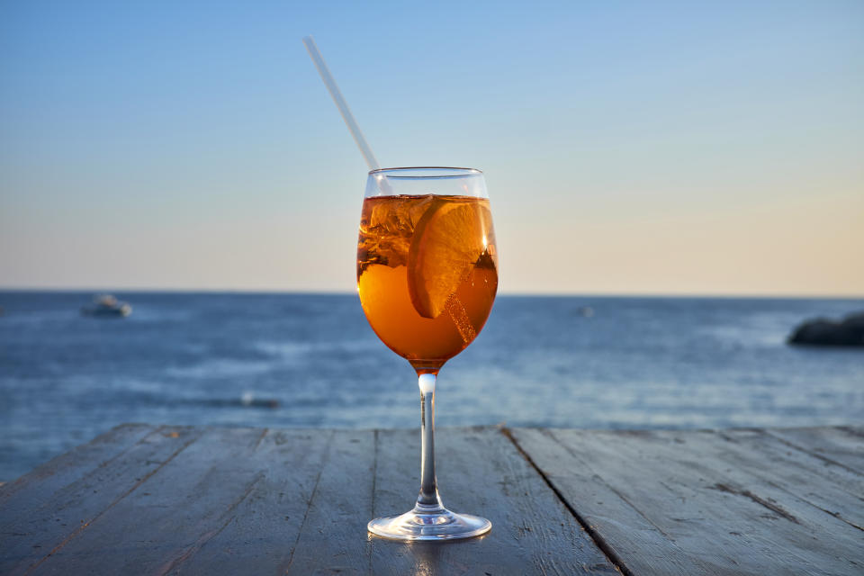 Glass of ice-cooled Spritz with orange slice in front of the sea