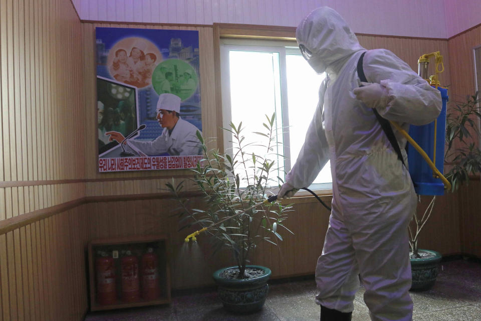 """FILE - In this Feb. 5, 2021, file photo, an official of the Hygienic and Anti-epidemic Center in Phyongchon District disinfects the corridor of a building in Pyongyang, North Korea. Isolated North Korea has continued to claim a perfect record in keeping out the coronavirus in its latest report to the World Health Organization, on Wednesday, April 7, 2021. At the beginning of the pandemic more than a year ago, North Korea shut its borders and described its efforts to keep out the virus as a """"matter of national existence."""" It banned tourists, jetted out diplomats and still severely limits cross-border traffic while quarantining tens of thousands of people who have shown symptoms. (AP Photo/Jon Chol Jin, File)"""
