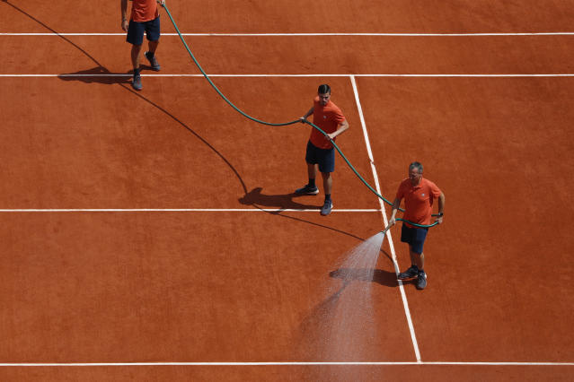 Stadium employees water the court before the men's final match of the French Open tennis tournament opposing Austria's Dominic Thiem to Spain's Rafael Nadal at the Roland Garros stadium in Paris, Sunday, June 9, 2019. (AP Photo/Pavel Golovkin)