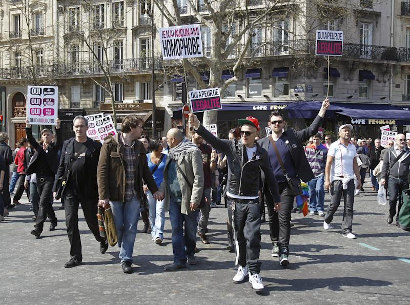 Pro-gay marriage demonstrators walk holding signs during a gathering held Bastille square in Paris, Sunday April 21, 2013. France's upper house of parliament, the Senate, adopted last Friday the law that would allow same-sex marriage and grant gay couples the right to adopt children. Returned to the National Assembly for a second reading, the bill's final vote is scheduled for April 23. Signs read: Who is afraid of Equality, I have no Homophobic Friend.(AP Photo/Remy de la Mauviniere)