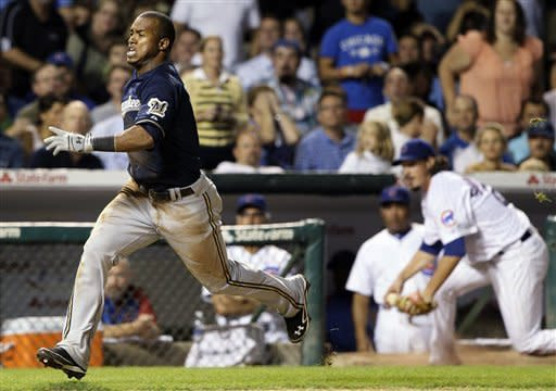Milwaukee Brewers' Jean Segura, left, runs to home after Chicago Cubs third baseman Luis Valbuena missed the catch during the seventh inning of a baseball game in Chicago, Wednesday, Aug. 29, 2012. (AP Photo/Nam Y. Huh)