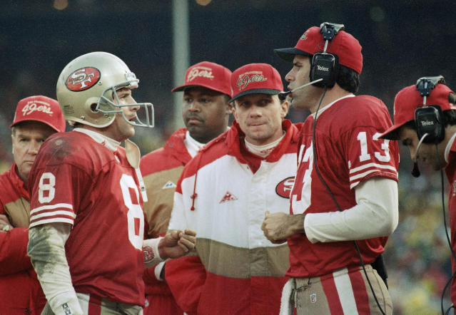FILE - In this Jan. 18, 1993 file photo, San Francisco quarterbacks Steve Young, left, Joe Montana and Steve Bono, right; hold court along the sideline as time ran down in the Niners' 30-20 NFC championship loss to the Dallas Cowboys at Candlestick Park in San Francisco. Soon after the Super Bowl matchup was set, Hall of Famer Joe Montana went to Twitter to send out a picture of his framed jerseys for the Kansas City Chiefs and the San Francisco 49ers. Montana won four Super Bowl titles in 14 years with the 49ers before finishing his career with two seasons on the Chiefs when he made one trip to the AFC championship game. (AP Photo/Paul Sakuma, File)