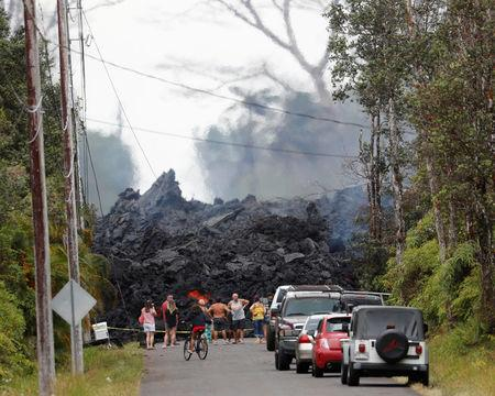 Onlookers gather in front of a fresh lava flow from the Kilauea volcano, in the Leilani Estates near Pahoa, Hawaii, U.S., May 26, 2018. REUTERS/Marco Garcia