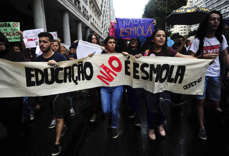 """Students hold a banner that reads in Portuguese """"Education is not charity"""" during a nation-wide education strike in Rio de Janeiro, Brazil, Wednesday, May 15, 2019. Federal education officials this month announced budget cuts of $1.85 billion for public education, part of a wider government effort to slash spending. (AP Photo/Bruna Prado)"""