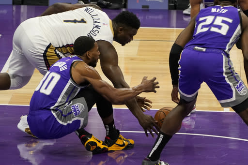New Orleans Pelicans forward Zion Williamson, left, scoops up the loose ball against Sacramento Kings forward Glenn Robinson III, second from left, during the first quarter of an NBA basketball game in Sacramento, Calif., Sunday, Jan. 17, 2021. (AP Photo/Rich Pedroncelli)