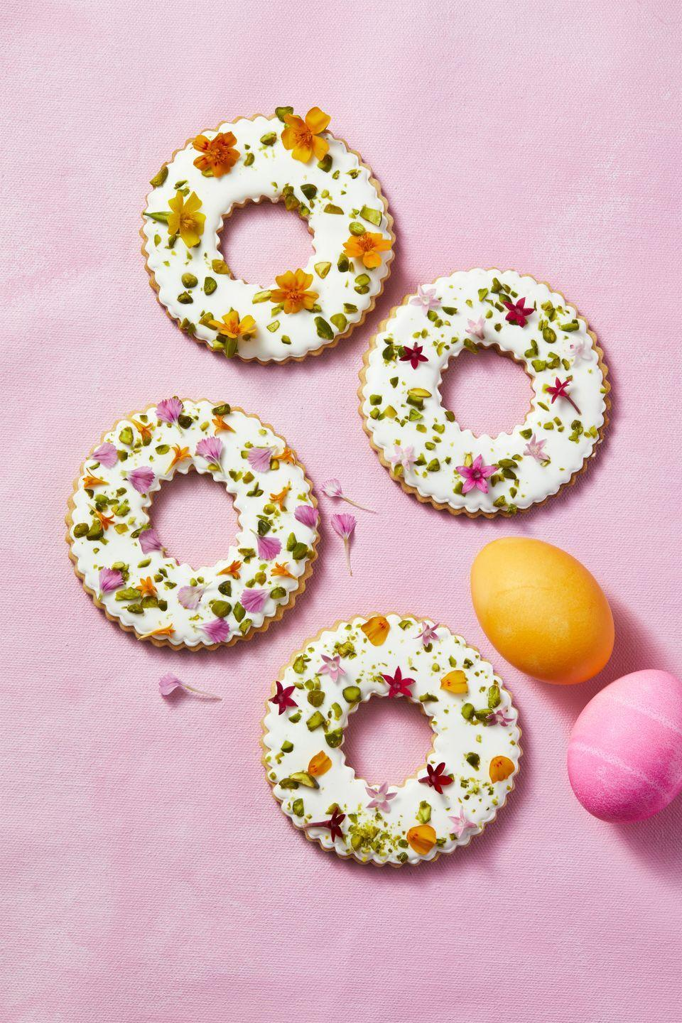 "<p>Use fluted circle cutters to cut rings from <a href=""https://www.goodhousekeeping.com/food-recipes/a6874/sugar-cookies-4477/"" rel=""nofollow noopener"" target=""_blank"" data-ylk=""slk:sugar cookie dough"" class=""link rapid-noclick-resp"">sugar cookie dough</a>, then bake and decorate with <a href=""https://www.goodhousekeeping.com/food-recipes/a28565256/royal-icing-recipe/"" rel=""nofollow noopener"" target=""_blank"" data-ylk=""slk:royal icing"" class=""link rapid-noclick-resp"">royal icing</a>. Before the icing sets, sprinkle with chopped pistachios and edible flowers. </p>"