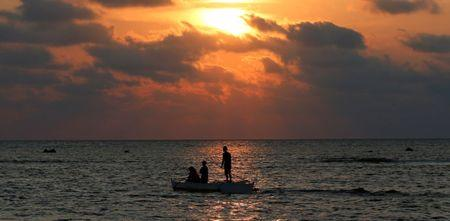Philippine fishermen steers a dinghy during sunset as they fish inside the shoal of the disputed Scarborough Shoal