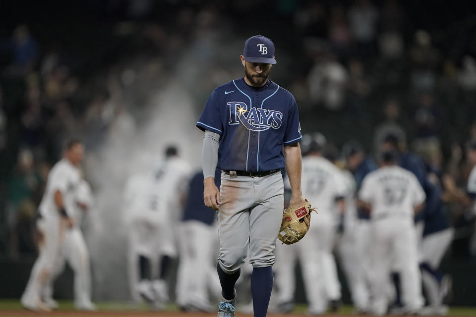 Tampa Bay Rays second baseman Brandon Lowe walks off the field as the Seattle Mariners celebrate after Kyle Seager drove in the winning run with a single in the ninth inning of a baseball game Thursday, June 17, 2021, in Seattle. The Mariners won 6-5. (AP Photo/Ted S. Warren)
