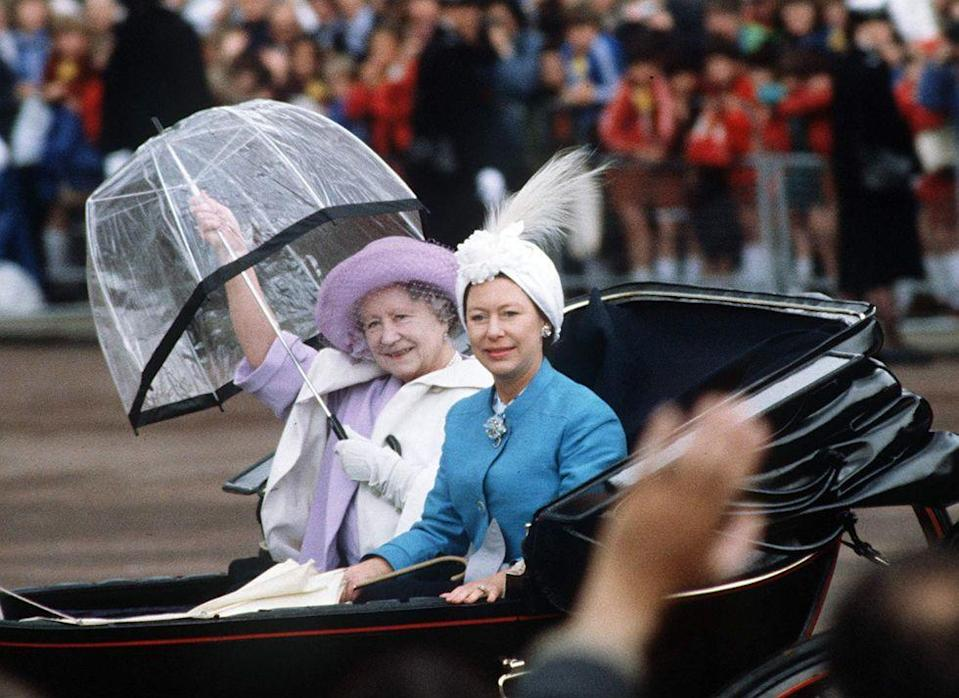 <p>The Queen Mother folds her umbrella as she and Princess Margaret participate in the Trooping the Color procession.<br></p>