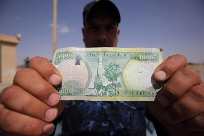 "<p>An Iraqi policeman displays a 10,000-Iraqi dinar banknote bearing an image of Mosul's iconic leaning minaret, known as the ""Hadba"" (Hunchback), on June 22, 2017, in Mosul. (Photo: Ahmad al-Rubaye/AFP/Getty Images) </p>"