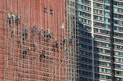 Construction workers climb bamboo scaffolding on a building in Hung Hom. Photo: Felix Wong