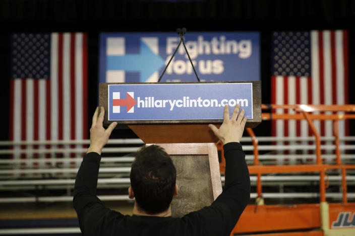 <p>A workman places placard on the podium ahead of Democratic presidential candidate Hillary Clinton's first-in-the-nation presidential primary campaign event, Tuesday, Feb. 9, 2016, at Southern New Hampshire University in Hooksett, N.H.<i> (Photo: Matt Rourke/AP)</i></p>