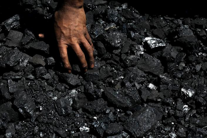 A hand separates pieces of coal.