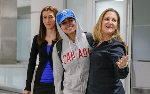 """<span>Rahaf Mohammed al-Qunun (C) accompanied by Canadian Minister of Foreign Affairs Chryistia Freeland (R), arrives at Toronto Pearson International Airport after escaping her """"abusive"""" family </span> <span>Credit: Reuters </span>"""
