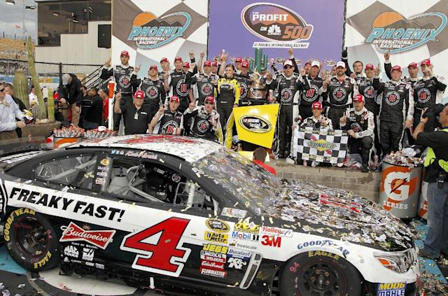 Kevin Harvick, standing to the right of the winner's trophy, joins his crew in posing for photographers in Victory Lane after winning the NASCAR Sprint Cup Series auto race Sunday, March 2, 2014, in Avondale, Ariz. (AP Photo/Ross D. Franklin)