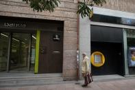 A man walks past branches of Bankia and Caixabank in Madrid