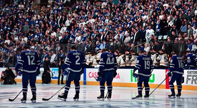 Players and fans stand for a moment of silence, after nine people died and 16 others were injured when a van mounted a sidewalk and struck multiple pedestrians along a stretch of one of Toronto's busiest streets. (Frank Gunn/CP)