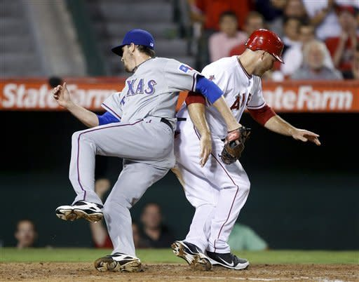 Texas Rangers relief pitcher Tanner Scheppers, left, collides with Los Angeles Angels' Chris Iannetta at home plate in the fourth inning of a baseball game in Anaheim, Calif., Tuesday, Sept. 18, 2012. (AP Photo/Jae C. Hong)