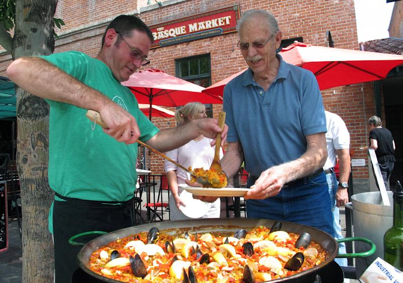 This Aug. 7, 2013 photo shows Tony Eiguren, left, owner of the Basque Market, serving a plate of paella to a lunch customer in Boise, Idaho. Each Wednesday and Friday, Eiguren and his staff make a big batch of paella in front of their store on Boise's historic Basque Block. The city's Basque Block downtown is the best place for learning more about the heritage. As early the late 1800s, Basques began settling in southwestern Idaho, many lured here to work as sheepherders. The Basque Block includes a museum, a market, restaurants, street art and historical signage. (AP Photo/Todd Dvorak)