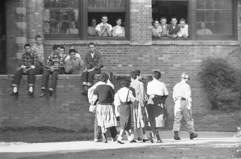 Los niños afroamericanos de Little Rock Central High School son escoltados.