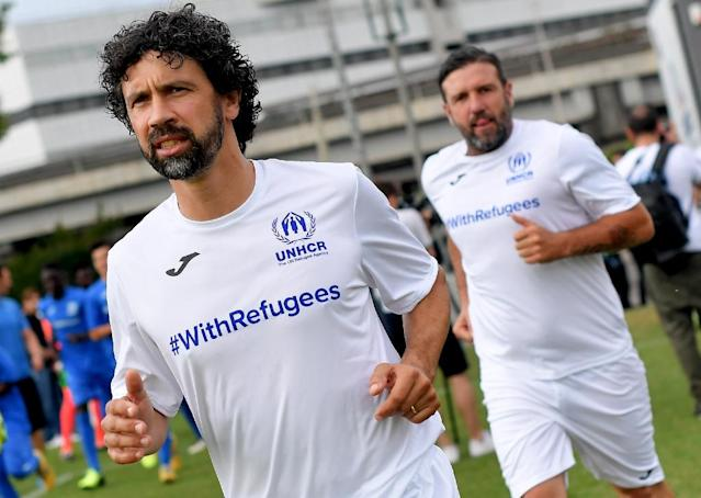 Former Italian footballer Damiano Tommasi leads out ex-French player Vincent Candela to take on the refugee team (AFP Photo/TIZIANA FABI)