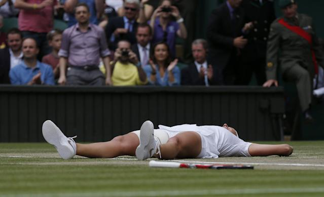 Petra Kvitova of Czech Republic lays on the court as she celebrates defeating Eugenie Bouchard of Canada in their women's singles final at the All England Lawn Tennis Championships in Wimbledon, London, Saturday July 5, 2014. (AP Photo/Sang Tan)