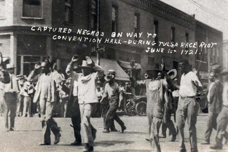 FILE - In this photo provided by the Department of Special Collections, McFarlin Library, The University of Tulsa, a group of Black men are marched past the corner of 2nd and Main Streets in Tulsa, Okla., under armed guard during the Tulsa Race Massacre on June 1, 1921. On May 31, 1921, carloads of Black residents, some of them armed, rushed to the sheriff's office downtown to confront whites who were gathering apparently to abduct and lynch a Black prisoner in the jail. Gunfire broke out, and over the next 24 hours, a white mob inflamed by rumors of a Black insurrection stormed the Greenwood district and burned it, destroying all 35 square blocks. Estimates of those killed ranged from 50 to 300. (Department of Special Collections, McFarlin Library, The University of Tulsa via AP, File)