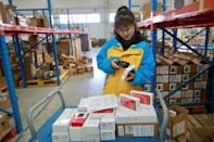 An employee checks items to be delivered to customers on Singles' Day, also known as the Double 11 shopping festival, at the warehouse of Suning Logistics Network in Shenyang