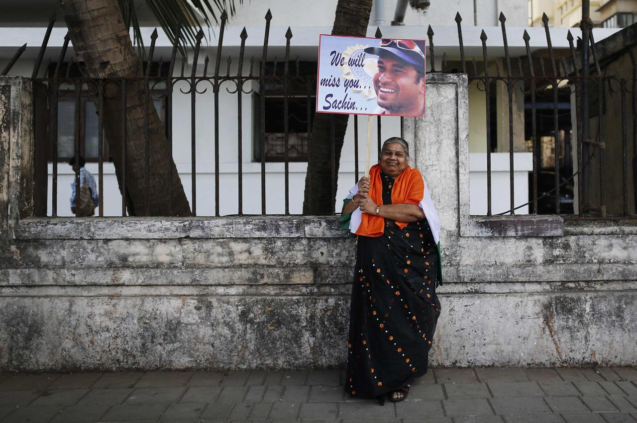 A cricket fan poses for photographers while holding a placard of cricketer Sachin Tendulkar outside a stadium in Mumbai November 14, 2013. Cricket-crazy India will have a lump in the throat as its favourite son, Tendulkar, walks out for one last time this week to play the game he has dominated for nearly a quarter of a century. The 'Little Master' will bring the curtain down on a glittering 24-year career at the age of 40 when he plays his 200th test match, against West Indies, at his home ground starting on Thursday. REUTERS/Danish Siddiqui (INDIA - Tags: SPORT CRICKET)