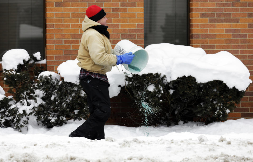 A man spreads salt on icy sidewalk in Chicago, Friday, Jan. 3, 2014. The snowstorm may finally have left town but a winter weather advisory is in effect for this evening when southerly winds are expected to kick up blizzard-like conditions. (AP Photo/Nam Y. Huh)