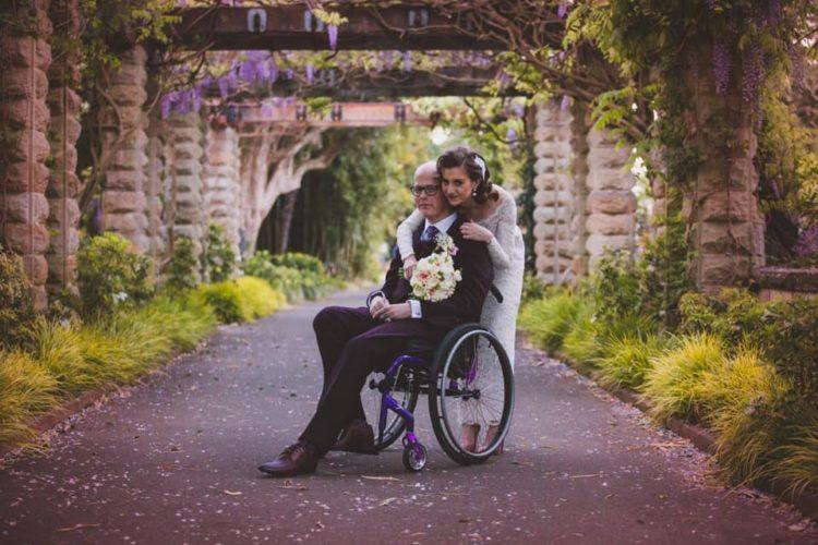 groom in wheelchair and bride hugging him from behind, under floral arrchways