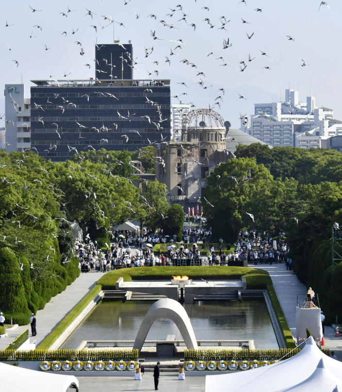 Doves fly over the cenotaph dedicated to the victims of the atomic bombing during a ceremony to mark the 73rd anniversary of the bombing at Hiroshima Peace Memorial Park in Hiroshima, western Japan, Monday, Aug. 6, 2018. The Atomic Bomb Dome is seen in center background. (Shingo Nishizume/Kyodo News via AP)