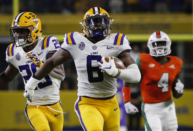 "LSU linebacker <a class=""link rapid-noclick-resp"" href=""/college-football/players/275539/"" data-ylk=""slk:Jacob Phillips"">Jacob Phillips</a> (6) returns an interception for a touchdown as Miami wide receiver Jeff Thomas (4) and LSU cornerback <a class=""link rapid-noclick-resp"" href=""/ncaaf/players/287374/"" data-ylk=""slk:Greedy Williams"">Greedy Williams</a> (29) look on. (AP Photo/Ron Jenkins)"