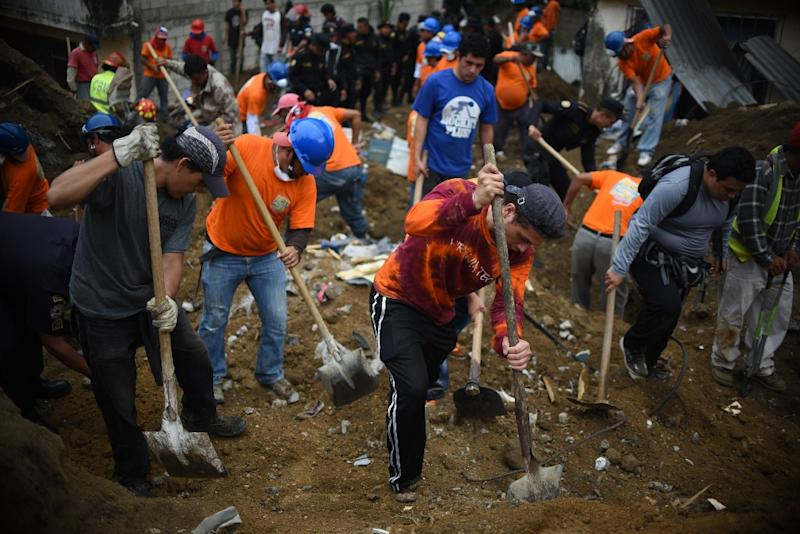 Volunteers take part in the search for victims in the village of El Cambray II, some 15 km east of Guatemala City, on October 3, 2015 after a landslide (AFP Photo/Johan Ordonez)