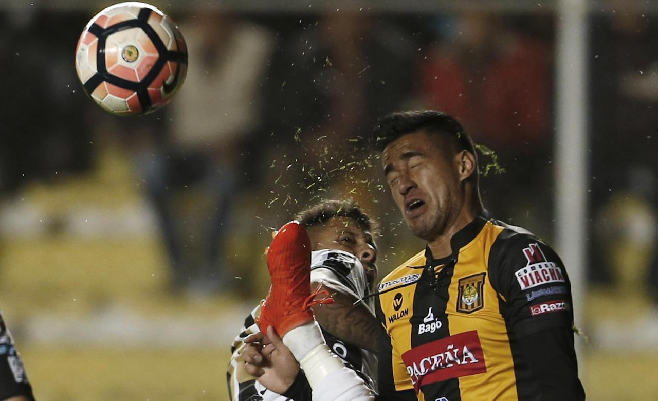 In this Thursday, Feb. 9, 2017 photo, Rodrigo Ramallo of Bolivia's The Strongest, right, is spattered with bits of grass after Mauricio Gomez of Uruguay's Wanderers kicks the ball during a Copa Libertadores soccer match in La Paz, Bolivia. The Strongest went on to win the match 4-0. (AP Photo/Juan Karita)
