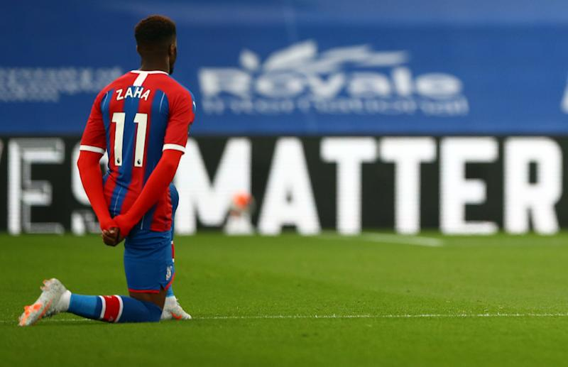 Crystal Palace's Ivorian striker Wilfried Zaha takes a knee in support of the Black Lives Matter movement during the English Premier League football match between Crystal Palace and Burnley at Selhurst Park in south London on June 29, 2020. (Photo by HANNAH MCKAY / POOL / AFP) / RESTRICTED TO EDITORIAL USE. No use with unauthorized audio, video, data, fixture lists, club/league logos or 'live' services. Online in-match use limited to 120 images. An additional 40 images may be used in extra time. No video emulation. Social media in-match use limited to 120 images. An additional 40 images may be used in extra time. No use in betting publications, games or single club/league/player publications. / (Photo by HANNAH MCKAY/POOL/AFP via Getty Images)