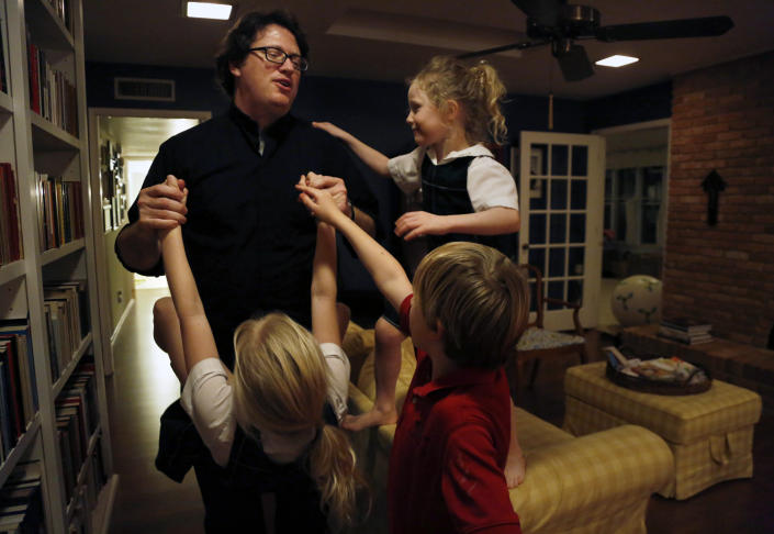In this Feb. 7, 2020, photo, Catholic Priest, husband and dad Joshua Whitfield plays with three of his four children Maggie, 9, Peter, 8, and Zoe-Catherine, 5, at their home in north Dallas. (AP Photo/Jessie Wardarski)