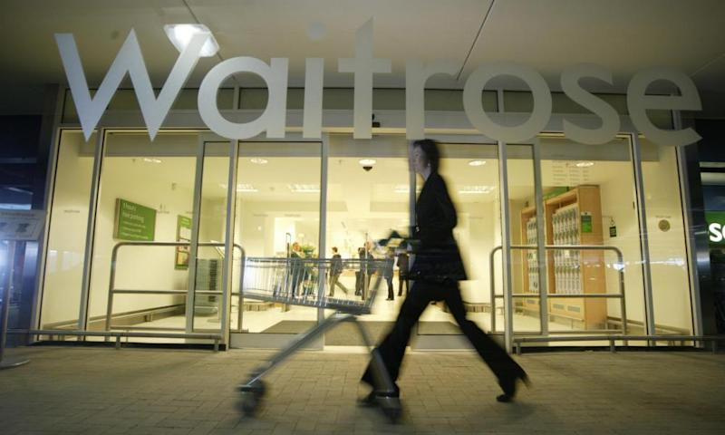 a shopper with a trolley passes a waitrose branch