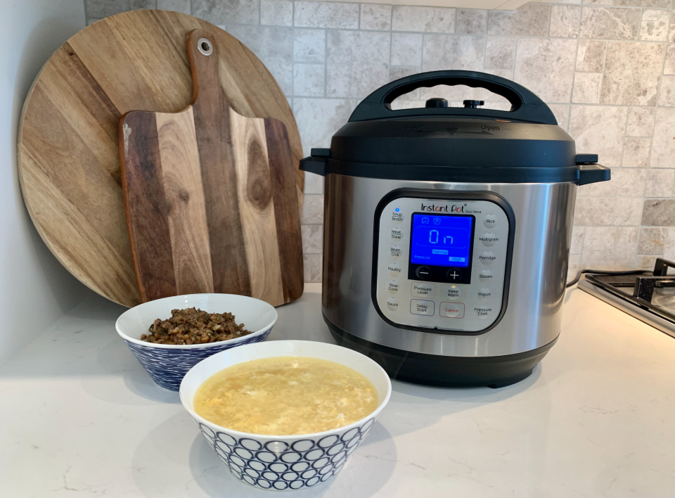 A 5.7L Instant Pot next to a bowl of chicken broth and a bowl of lentils