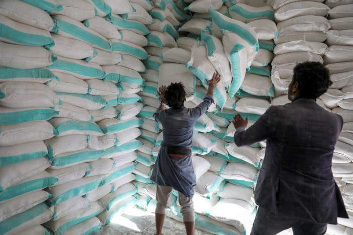FILE PHOTO: Workers handle sacks of wheat flour at a World Food Programme food aid distribution center in Sanaa