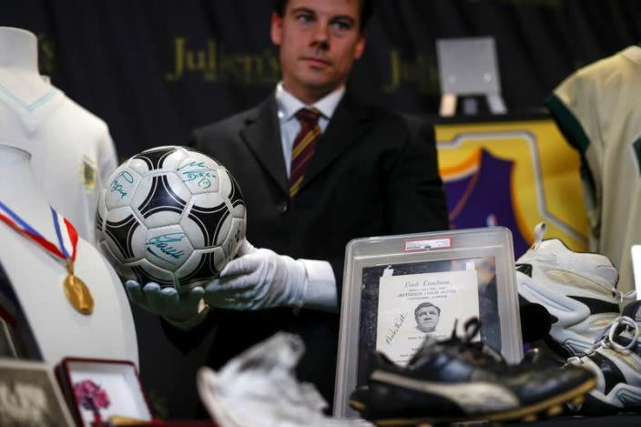 """Kendall Capps holds a soccer ball autographed by late soccer star Diego Armando Maradona ahead of the upcoming """"Sports: Legends"""" auction in Culver City"""