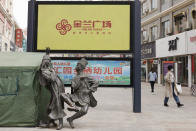 Pedestrians walk by statutes depicting Uyghurs in traditional garb dancing on a shopping street in Aksu, in northwestern China's Xinjiang Uyghur Autonomous Region, on March 18, 2021. Four years after Beijing's brutal crackdown on largely Muslim minorities native to Xinjiang, Chinese authorities are dialing back the region's high-tech police state and stepping up tourism. But even as a sense of normality returns, fear remains, hidden but pervasive. (AP Photo/Ng Han Guan)