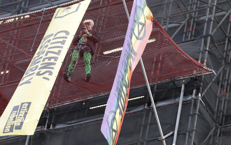 A climate protester demonstrates with banners on the scaffolding covering the Elizabeth Tower that houses the Big Ben clock in London, Friday, Oct. 18, 2019. (AP Photo/Kirsty Wigglesworth)