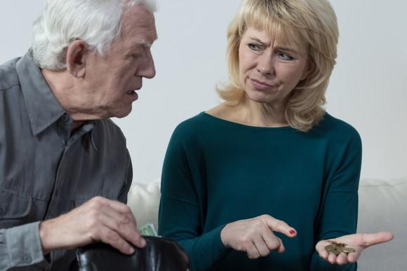 A confused elderly man looking at pocket change held by a woman next to him.