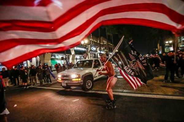 Crowds Gather In Huntington Beach To Protest COVID-19 Curfew