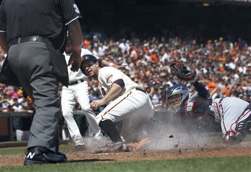 San Francisco Giants' Brandon Belt slides into homeplate safely past Atlanta Braves catcher Brian McCann (16) to score on a on a single by Brandon Crawford during the fourth inning of the National League MLB baseball game in San Francisco, Sunday, May 12, 2013. (AP Photo/Tony Avelar)